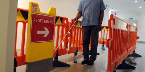 Photograph of a set of roadworks signs and barriers set up inside with a symbol cane user passing through