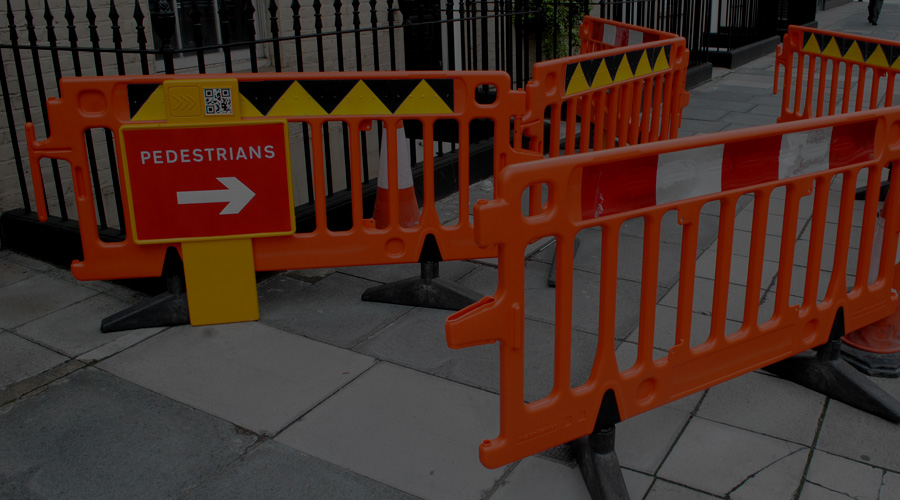 Photo of a roadworks set up featuring a new sign plus a yellow and black triangle pattern and tactile dots on the pedestrian side of the barriers