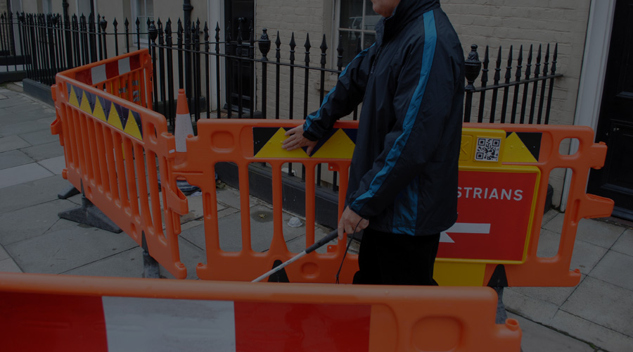 Photo of a long cane user following a line of tactile dots through a roadworks site
