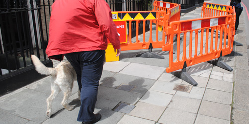 Photograph of a guide dog user approaching a modified set of roadworks