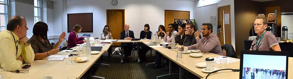 Twelve people sit around a meeting table