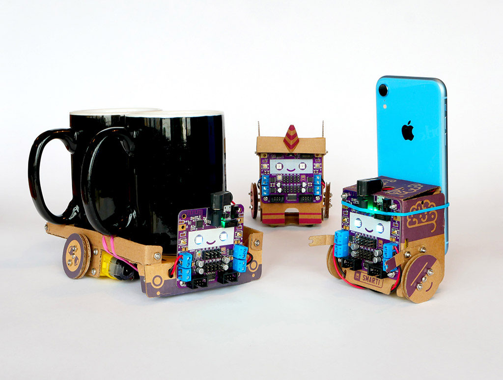 Three cardboard robots. One is wide and flat and carries two large ceramic mugs on it's back, one is a pink unicorn, one is smalledr and cube-shaped and carries a smartphone on its back.