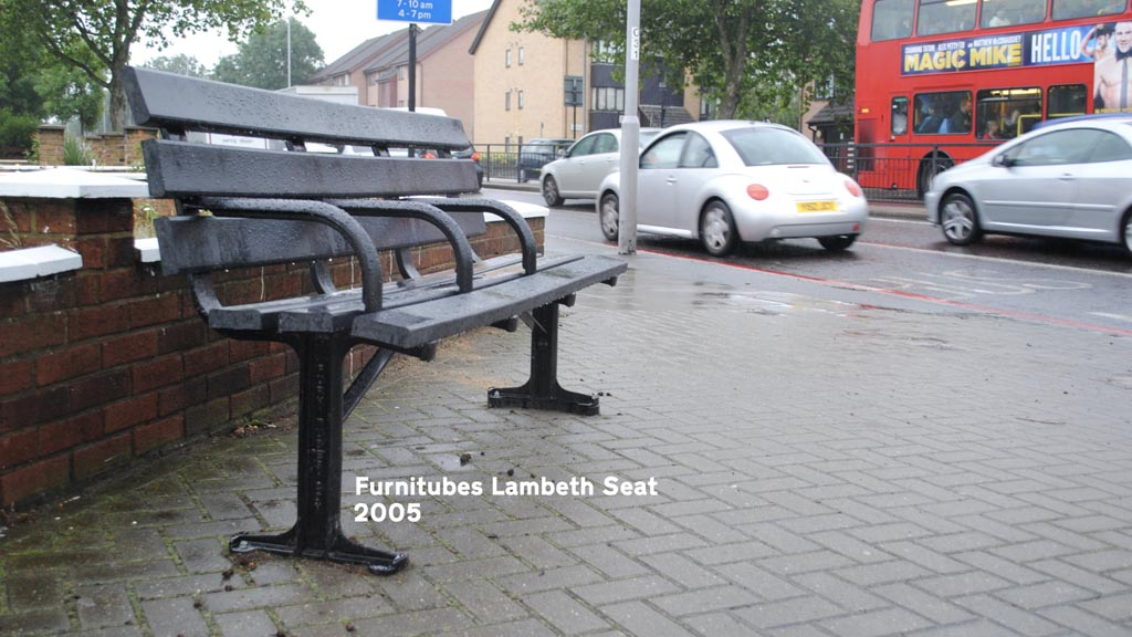 Photo of a bench on an outer London street. It is black with a metal frame and plastic slats.
