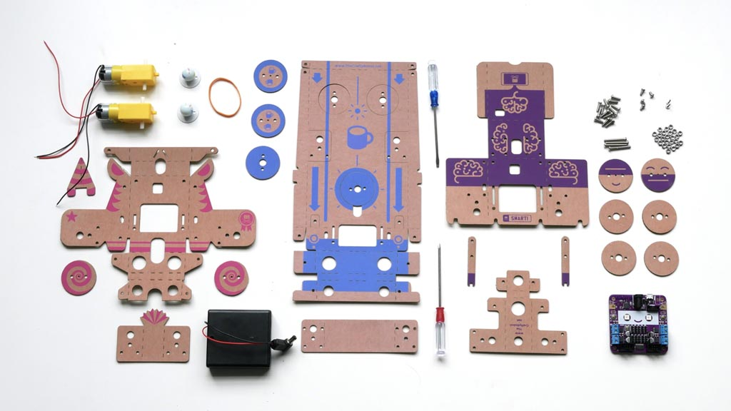 Photo of the components from a cardboard robot kit arranged neatly. It includes die cut cardboard parts, motors, marbles, a battery box and a small purple circuit board with a smiling face on it