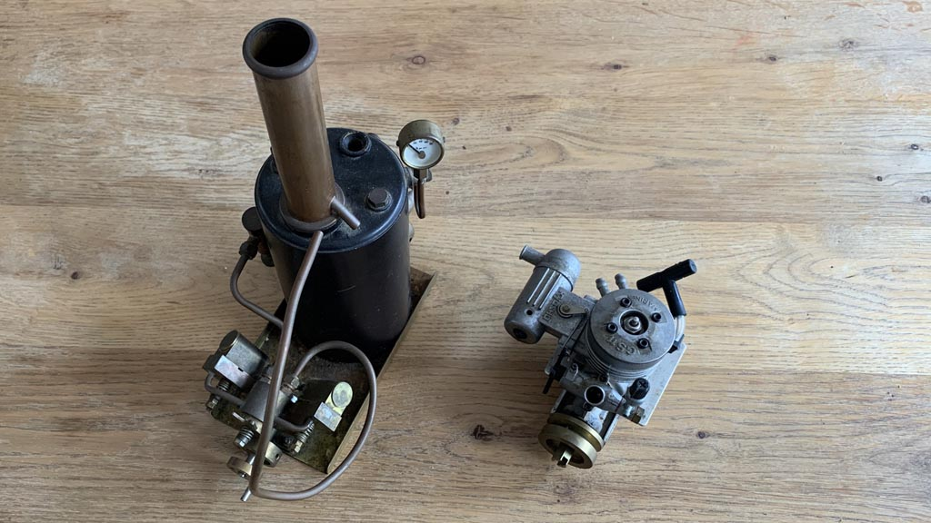Photo of a model steam engine and a toy petrol engine on a table