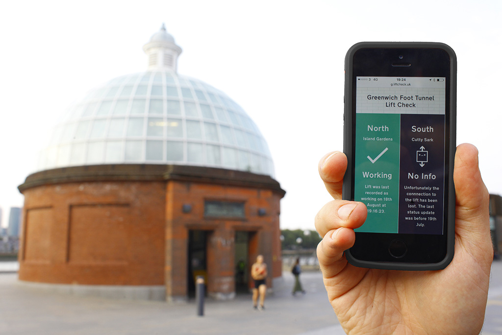 Smartphone displaying lift status app in front of Greenwich Foot Tunnel entrance. App reads ' North, Island Gardens, Working; South, Cutty Sark, No Info'