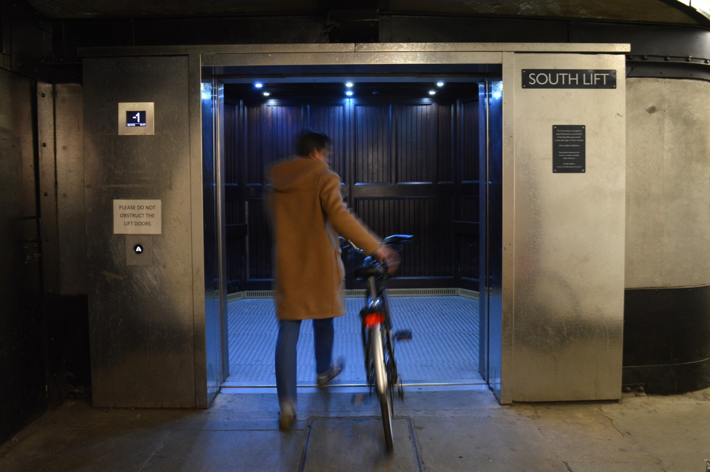 Photo of a cyclist entering a large lift.