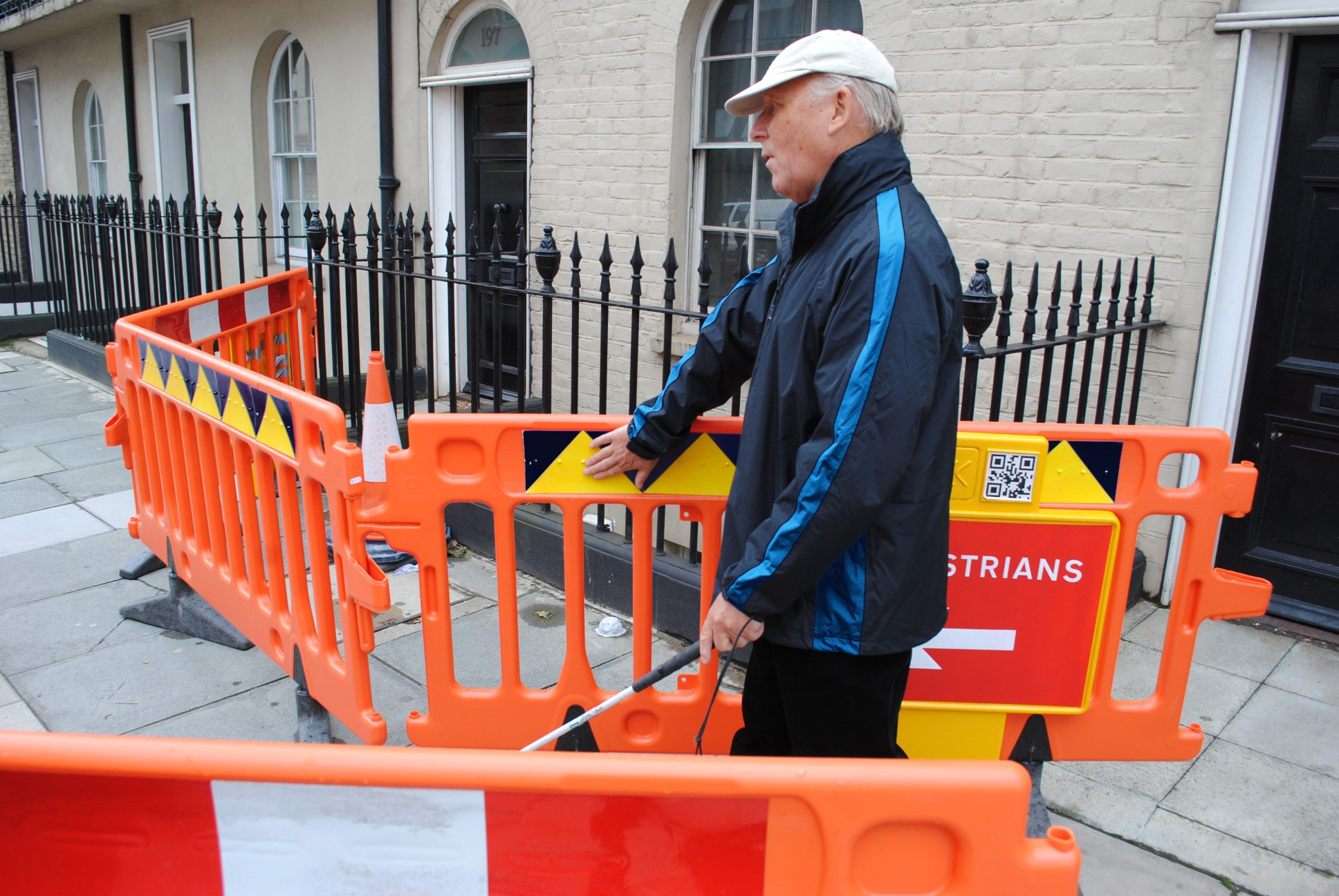 Photo of a long cane user negotiating a road works site. His free hand is following a line of tactile dots on the barriers.