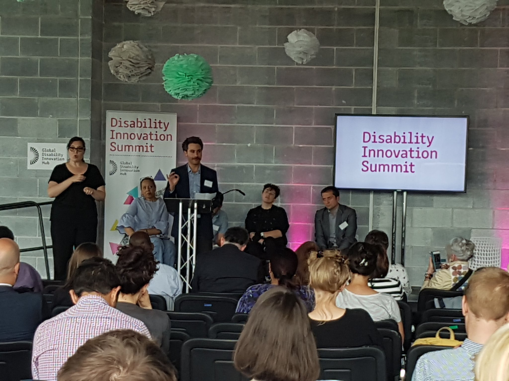 Ross Atkin speaks from lectern, Disability Innovation Summit is written on a screen behind him. As sign language interpreter stands to his right.