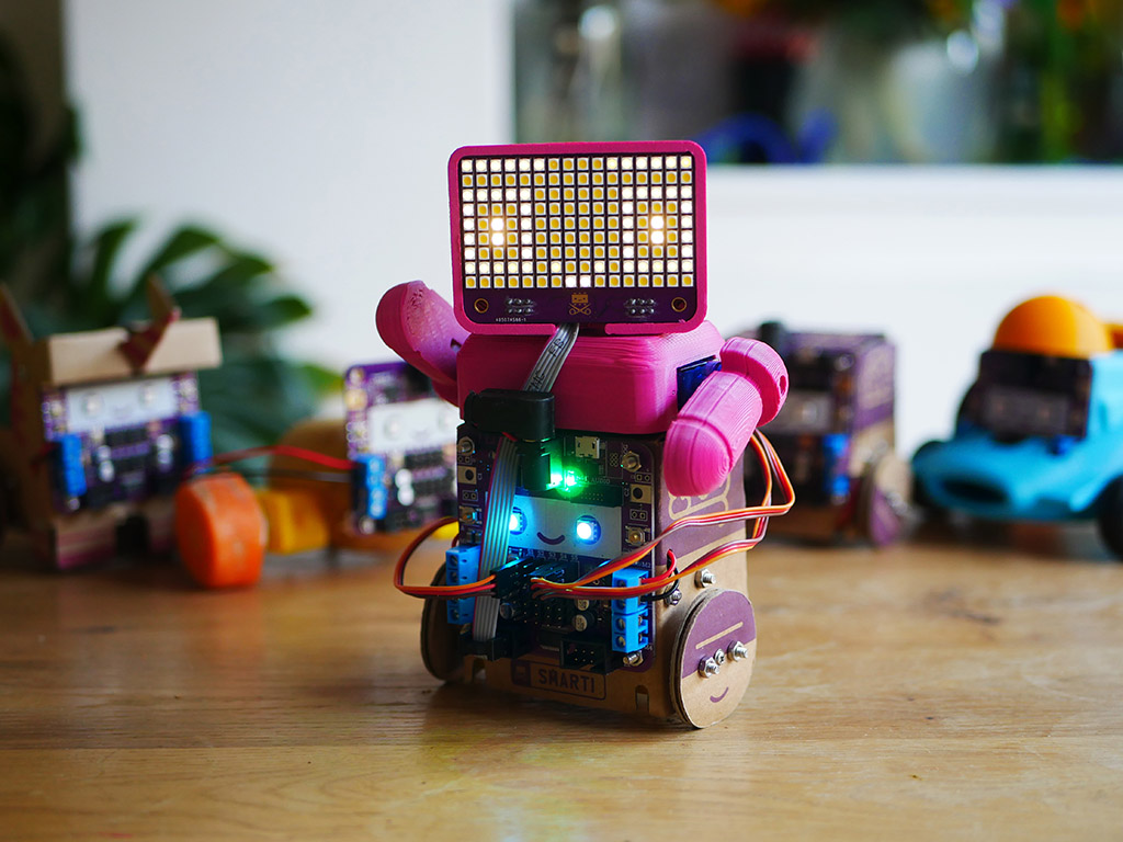 Cube-shaped cardboard robot with pink robot head and torso on top, with one arm raised and on the head a rectangular LED matrix displaying a smiling face